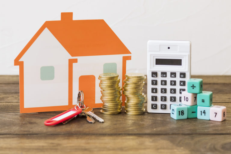 house key stacked coins calculator and math blocks on wooden table Porteo