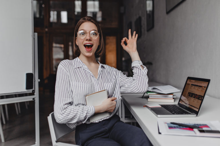 joyful girl office worker shows ok sign portrait of woman in pants and light blouse at workplace Porteo