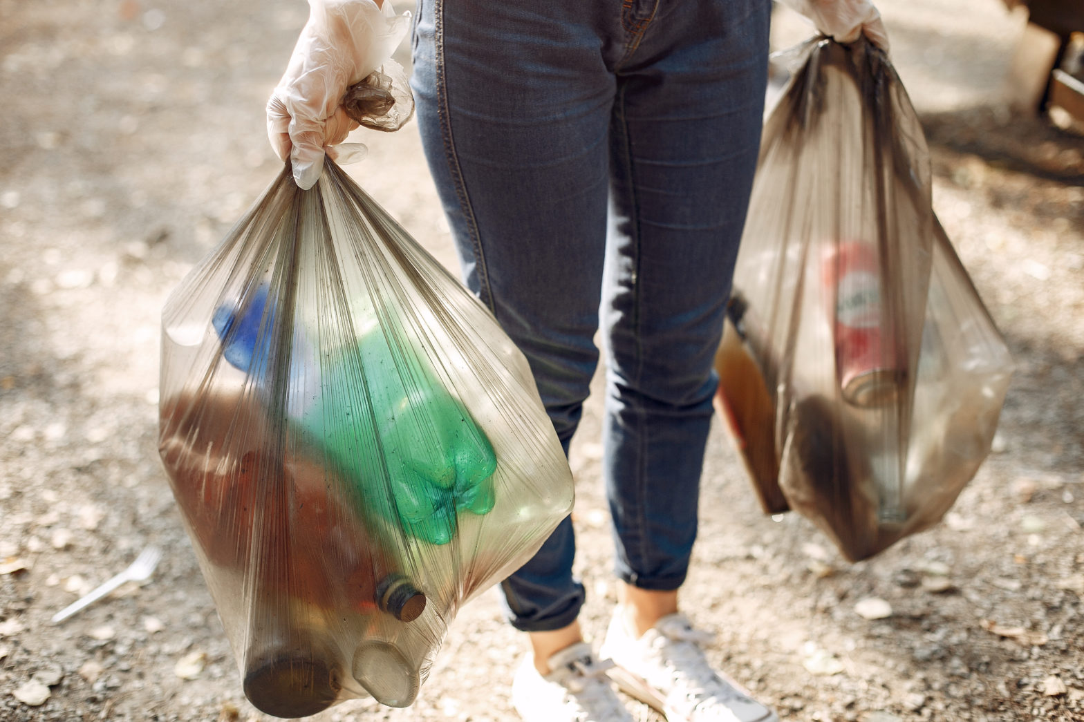 girl collects garbage in garbage bags in park Porteo
