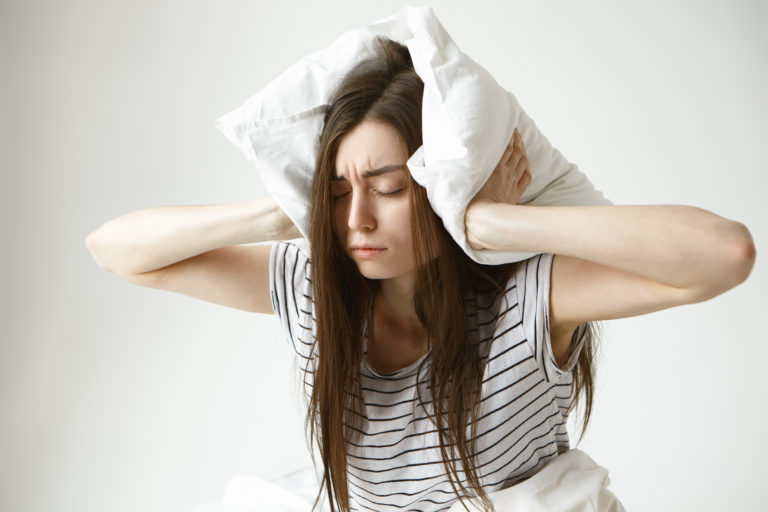 isolated portrait of stressed young brunette woman wearing striped pajamas covering ears with white pillow feeling frustrated as she can t fall asleep at night because of her snoring husband Porteo